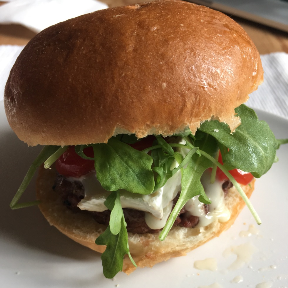 a burger with rocket and melting goat cheese on a brioche bun